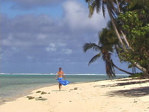 A vacationer strolls down a tropical beach Footage