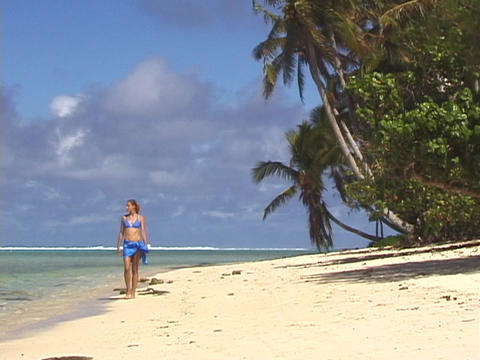 A woman strolls across a tropical beach Stock Video Footage