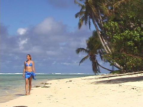 A woman strolls across a tropical beach Footage