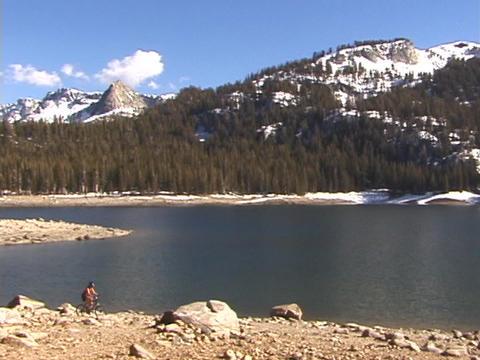 A biker rides next to a lake Stock Video Footage
