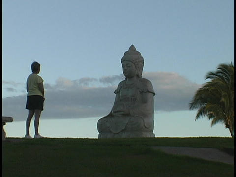 A tourist stands in front of a Buddha statue Stock Video Footage