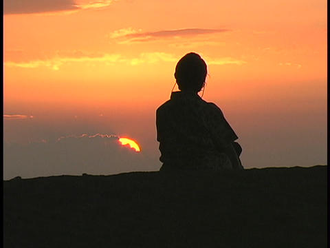 A woman sits and watches the sky Stock Video Footage