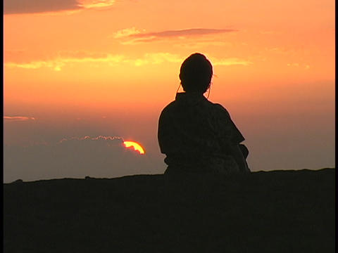 A woman sits and watches the sky Live Action