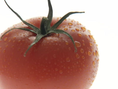 Water droplets glisten on a ripe, red tomato Footage