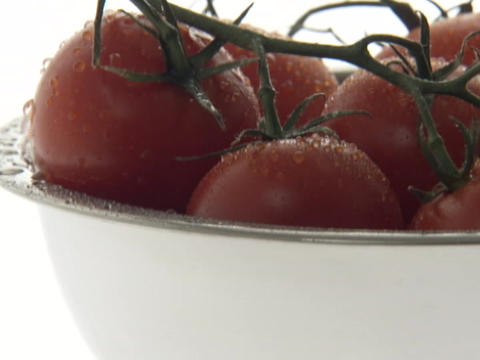 Water droplets drip down cherry tomatoes in a bowl Footage