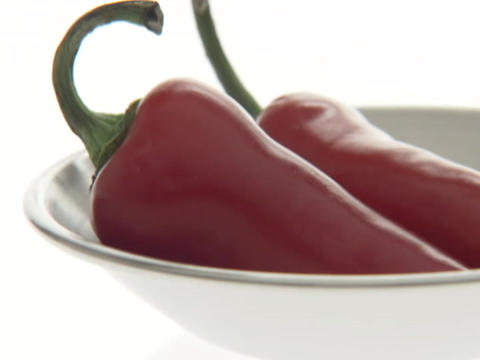 Red peppers sit in a small bowl Footage