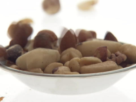 Mixed nuts drop into a small bowl Stock Video Footage