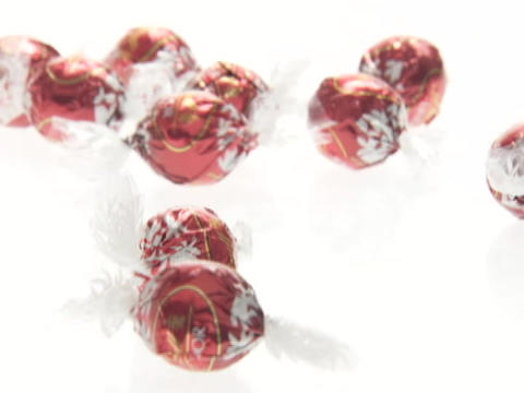 Candies roll onto a surface next to one another Footage