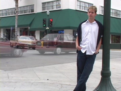 A man leans against a street lamp while traffic passes by Stock Video Footage