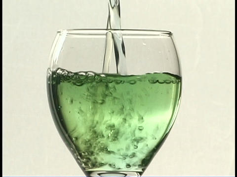 A green liquid pours into a wine glass Footage