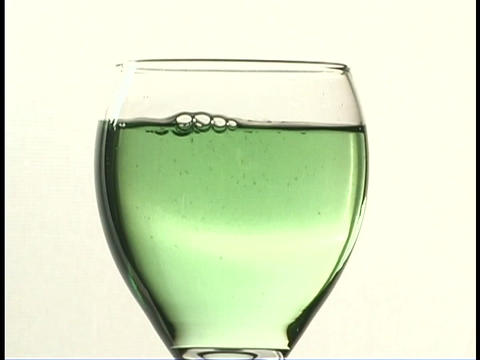 A green liquid pours into a wine glass Stock Video Footage