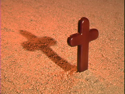 A shadow rises behind a Christian cross Footage