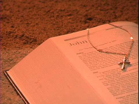A gold cross rests cross a Bible over the book of John Stock Video Footage