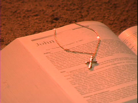 A gold cross rests cross a Bible over the book of John Footage