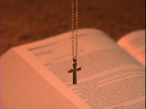 A gold cross hangs over a Bible open to the book of John Footage