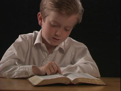 A young boy reads a Bible Stock Video Footage