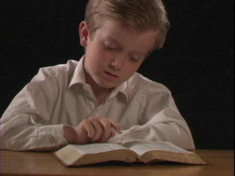 A young boy reads a Bible Live Action
