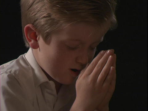 A young boy prays Stock Video Footage
