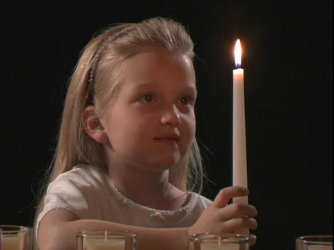 A young girl watches a flame of a candle Stock Video Footage