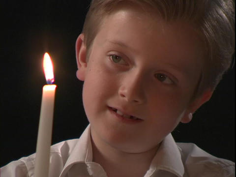 A young boy watches the flame on a candle Stock Video Footage