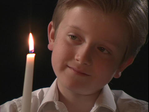 A young boy watches the flame on a candle Footage