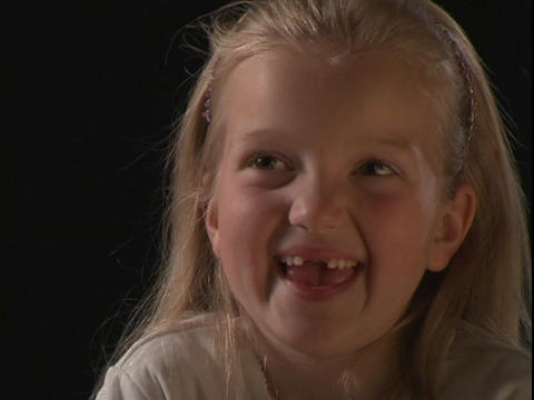 A young girl smiles and makes silly faces Footage