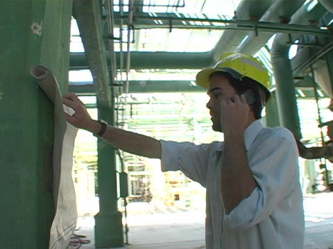 A contractor talks on the phone as he examines documents Stock Video Footage