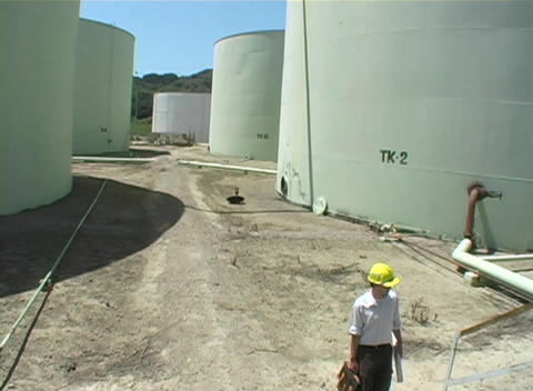 Medium shot of contractor walking near industrial storage... Stock Video Footage