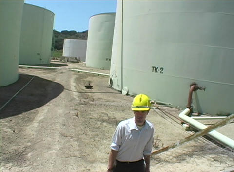 Medium shot of contractor walking near industrial storage tanks at construction site Footage