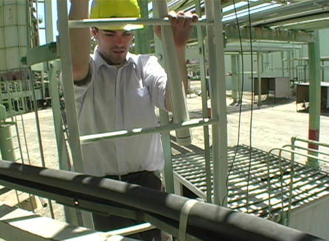 Close up of contractor descending fixed rail ladder at construction site Footage