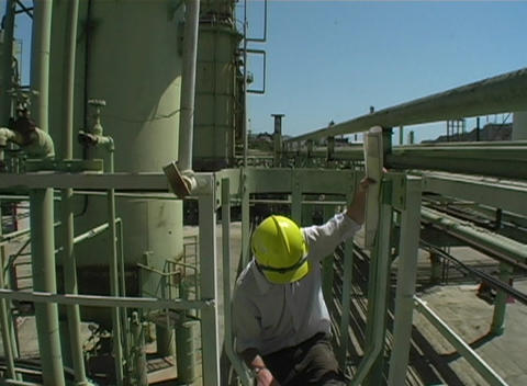 Pan-down of a contractor descending a fixed ladder with... Stock Video Footage