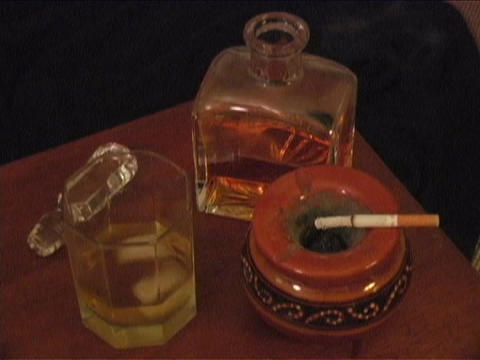 A cigarette burns in an ashtray with ice melting in a glass next to a bar bottle of liquor Footage