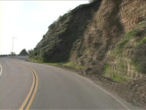 A narrow two lane road curves around mountains Stock Video Footage