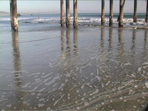 Ocean waves roll in under pier pilings Stock Video Footage
