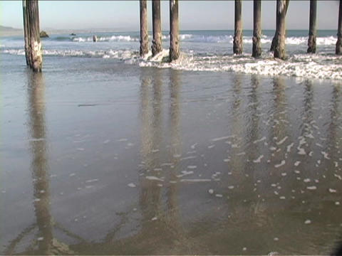 Ocean waves roll in under pier pilings Footage