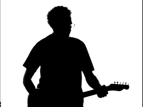 A guitarists is silhouetted while he plays Footage