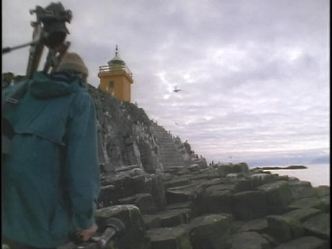 A man and woman carry camera equipment towards a lighthouse Stock Video Footage