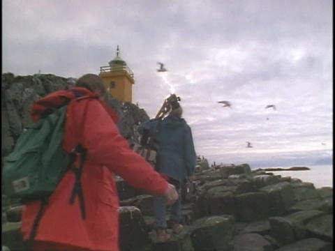 A man and woman carry camera equipment towards a lighthouse Footage