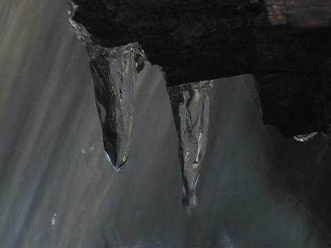 Water flows over icicles attached to a rock Stock Video Footage