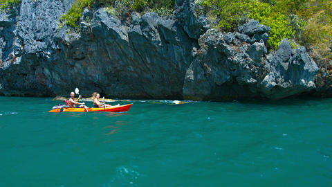 Adventurous tourists. kayaking past the rugged. rocky coastline of a tropical is Footage