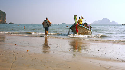 Tourist carrying his suitcase to a tour boat. waiting in the shallows. just off Footage