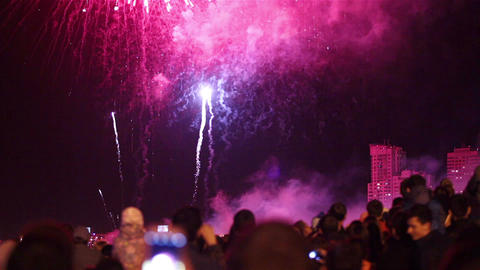 Spectators watch fireworks in the sky over the city Footage