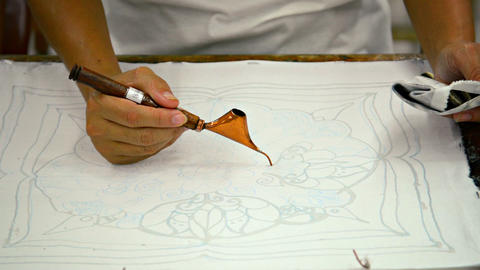 Artist creating a traditional work of art. Batik. Spouted tool - canting. Tjanti Live Action