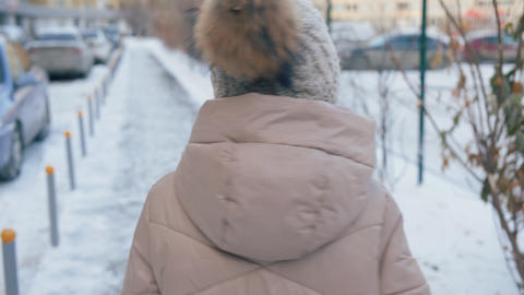 Girl walking on street and turning to look back at winter day Live Action