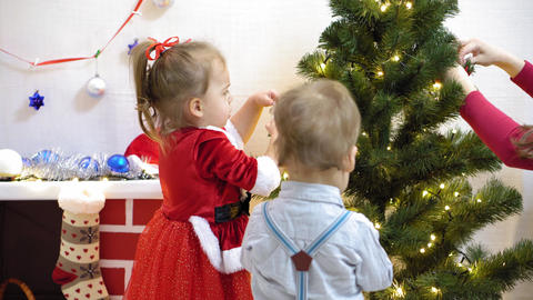 baby and pregnan mom hang red ball toy on Christmas tree. happy childhood Live Action