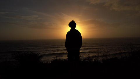 This stock video shows a silhouette of a man watching the sunset in a cliff over the sea Live Action