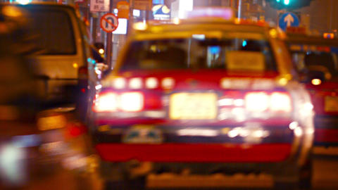 Long Line of Taxis Cruises down an Urban Street at Night Footage