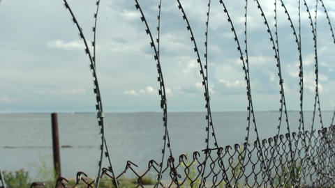 Sea behind barbed wire fences Footage