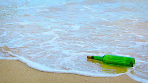 Green Glass Wine Bottle Rolling in the Surf. with Sound Footage