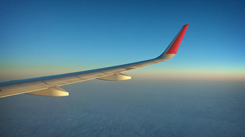 High Altitude Airborne Shot of an Airplane Wing over a Cloudy Horizon Footage